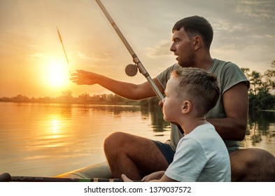 Happy Father and Son together fishing from a boat at sunset time in summer day under beautiful sky on the lake. Togetherness, Family, Recreating concept.