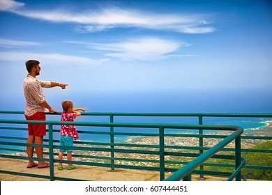 happy father and son, tourists enjoying the fascinating view on Atlantic ocean coastline from observation deck of Pico Isabel de Torres
