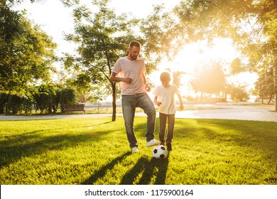 Happy father spending time with his little son at the park, playing football on a grass