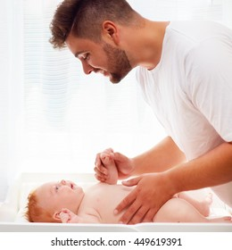 happy father taking care of infant baby