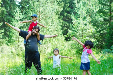 Happy father and three children in nature