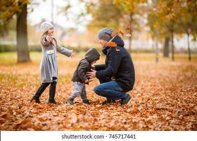 Happy father with two his children playing in autumn park.