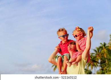 happy father with two kids on shoulders at sky