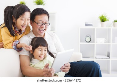 happy father using tablet pc with little girls