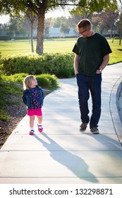Happy father walking and talking with his adorable toddler daughter