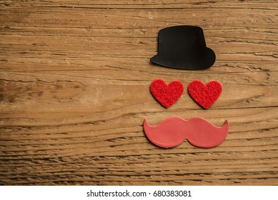 Happy Father's day background or card. red sign of mustache with two red heart - eyes. empty copy space for inscription. happy Valentine's day background. black hat and mustache