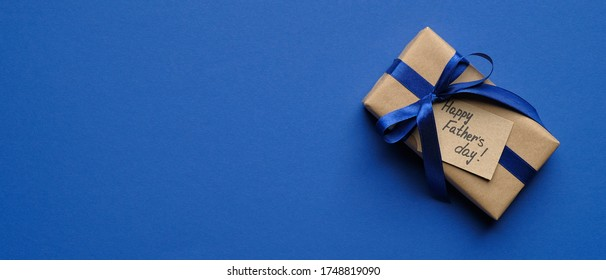 Happy Fathers Day banner template. Top view vintage gift box with label Happy Father's Day on blue background with copy space.