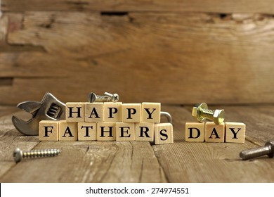 Happy Fathers Day blocks with tools on a rustic wood background