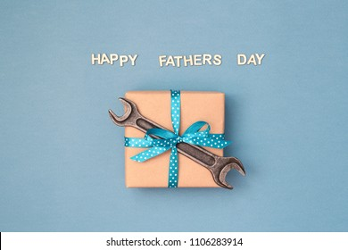 Happy Father's day card with gift box wrapped in kraft paper tied with blue ribbon in polka dots and wrench on blue grey background. Greeting card with wooden letters.