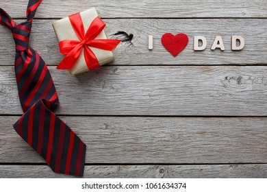Happy Fathers Day card with male presents, love dad letters, present and red and black striped necktie on rustic wood background, copy space, top view