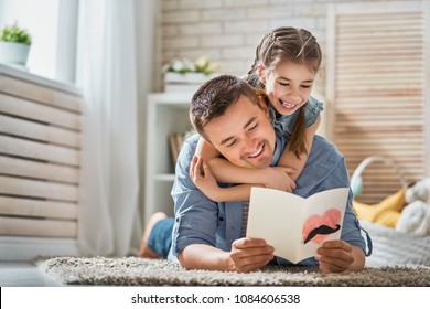 Happy father's day! Child daughter congratulating dad and giving him postcard. Daddy and girl smiling and hugging. Family holiday and togetherness.