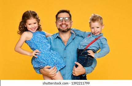 Happy father's day! Children daughter and son congratulates dad  on yellow backgraund