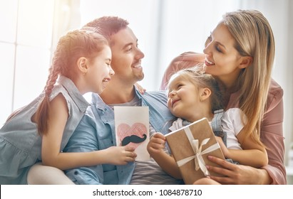 Happy father's day! Children daughters and their mom are congratulating dad and giving him postcard and gift box. Daddy and girls smiling and hugging. Family holiday and togetherness.