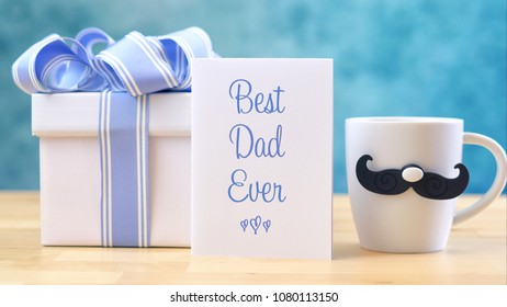Happy Father's Day close up of Best Dad Ever greeting card and coffee mug on table.