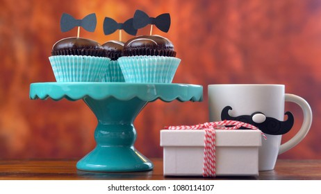 Happy Father's Day close up of gift, cupcakes and card against rustic wood background.