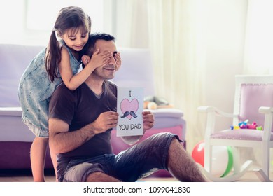Happy Father's Day Concept. Child Daughter Hiding Surprise Postcard Present for Her Dad.