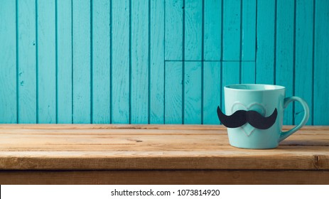 Happy Fathers day concept with coffee cup and mustache over wooden background