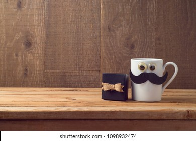 Happy Fathers day concept with coffee cup, mustache and gift box over wooden background