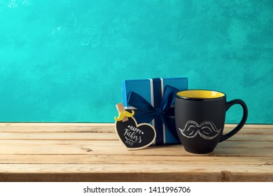 Happy Father's day concept with coffee mug and gift box over wooden background