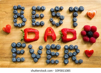 "Happy Father's Day concept image with Strawberries and Blueberries inscription ""BEST DAD EVER"" on a rustic cutting board."