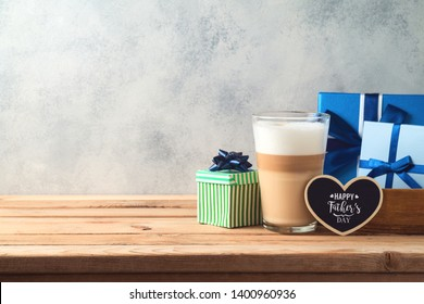 Happy Father's day concept with latte macchiato coffee and gift box over wooden background