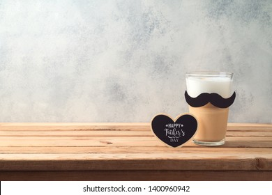 Happy Father's day concept with latte macchiato coffee and mustache over wooden background