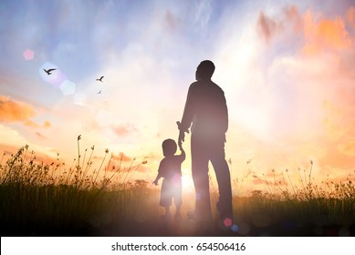 Happy Father's Day concept: Silhouette Father and son standing on meadow sunrise background
