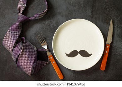 Happy fathers day concept. Table setting - plate, tie, cutlery and napkin on grey stone table. Top view flat lay background.