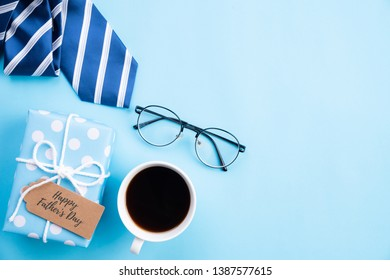 Happy fathers day concept. Top view of blue tie, beautiful gift box, coffee mug, glasses with LOVE DAD text on bright blue pastel background.