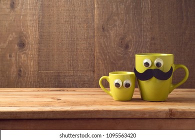 Happy Fathers day concept with two coffee cups as father and son over wooden background