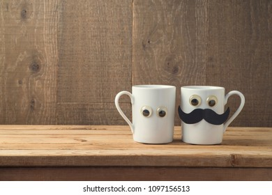 Happy Fathers day concept with two coffee cups as father and son funny characters over wooden background