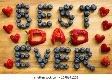 Happy Father's Day conceptual image with BEST DAD EVER inscription with strawberries and blueberries and heart shaped strawberries on rustic cutting board.
