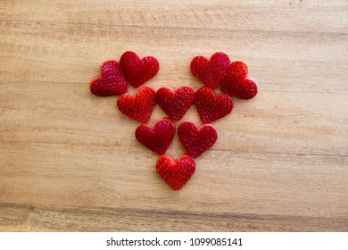 Happy Father's Day conceptual Image with heart-shaped strawberries on rustic cutting board.