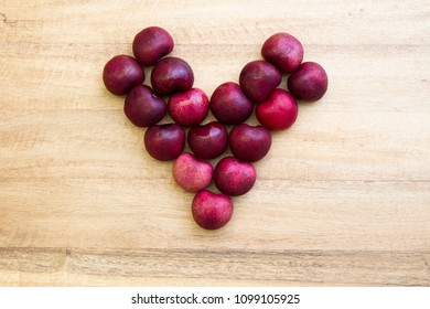 Happy Father's Day conceptual Image with heart-shaped cherries on rustic cutting board.