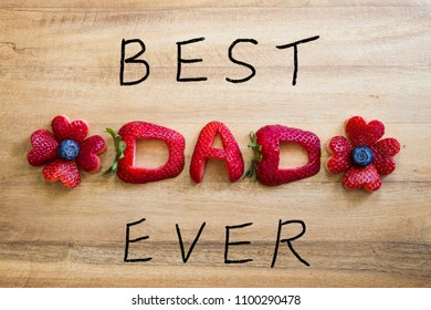 Happy Father's Day conceptual image with BEST DAD EVER inscription with Strawberries and handwriting on rustic wooden cutting board.