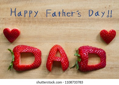 Happy Father's Day conceptual image with DAD inscription with Strawberry, heart shapes, and Happy Father's Day handwriting on wooden cutting board. With copy space.