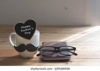 Happy fathers day. Cup and card with mustache on table on brown background concept.
