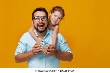 happy father's day! cute dad and daughter hugging on colored yellow background