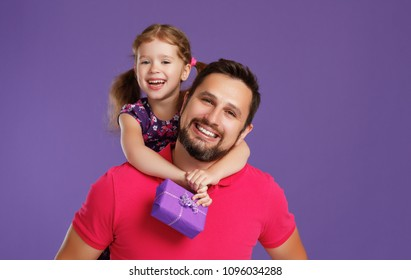 happy father's day! cute dad and daughter hugging on colored violet background
