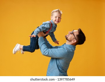 happy father's day! cute dad and son hugging on colored yellow background