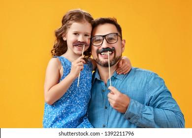 Gelukkige vaderdag! grappige vader en dochter met snor gek rond op gekleurde gele achtergrond