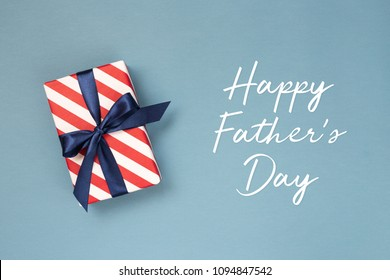 Happy Father's day greeting card with decorated gift box on blue background. Top view.