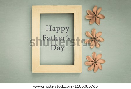 happy fathers day message in wooden frame with flower on wood texture background vintage tone