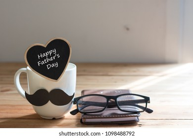 Happy fathers day.Cup with mustache on table on brown background