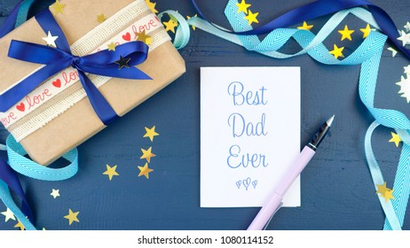 Happy Father's Day overhead with decorated borders, gift and greeting card on dark blue wood table.