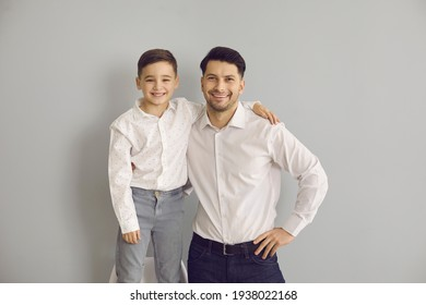 Happy father's day. Portrait of dad with little son hugging and looking at camera on gray background. Cute son is standing on a chair to be as tall as dad. Concept of fatherhood. Place for text.