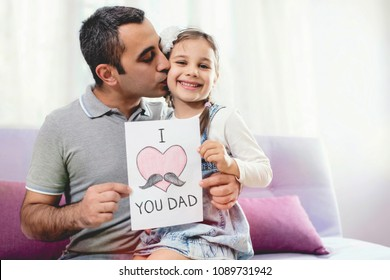 Happy Father's Day Portrait. Surprised Dad Holding Postcard Gift and Kissing Her Smiling Child.