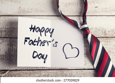 Happy fathers day sign on paper and colorful tie laid on wooden floor backround.