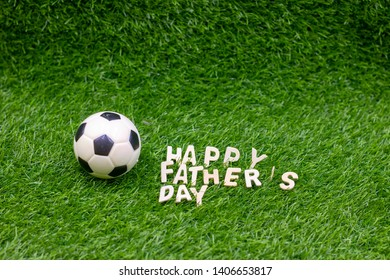 Happy Father's Day to Soccer with football are on green grass.