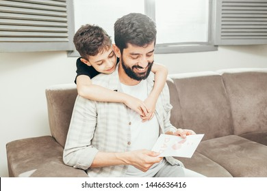 Happy father's day! Son congratulating dad and giving him a greeting card. Daddy and son smiling and hugging. Family holiday and togetherness.